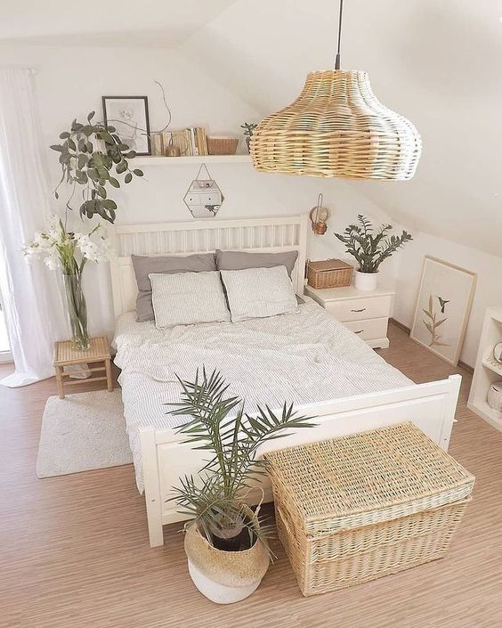 a small neutral bedroom with white furniture, a wicker lamp and a chest, potted plants and blooms and a ledge with artworks