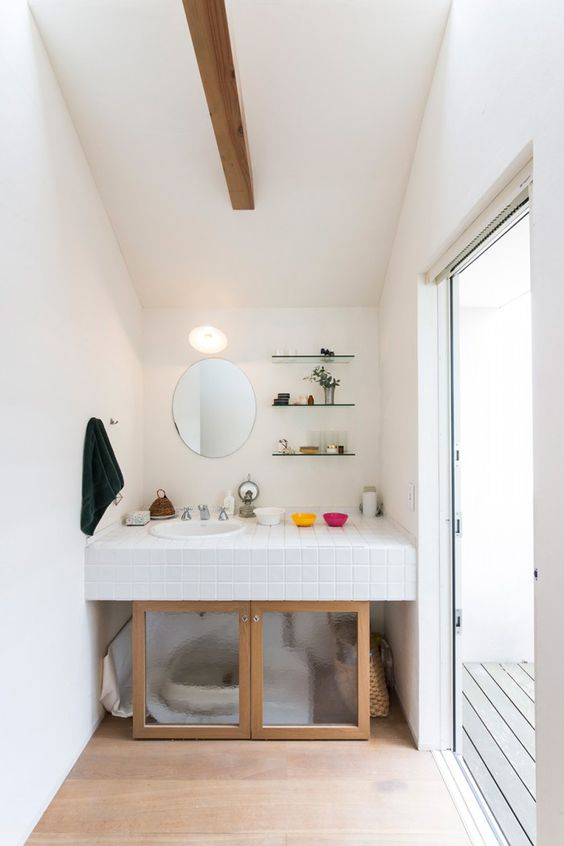a space under a sink wiht a cat toilet and frosted glass doors plus access to it from both sides