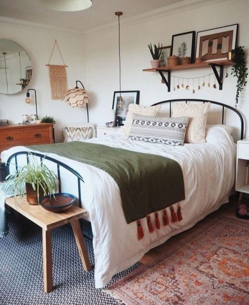 a spring boho bedroom in neutrals, with a metal bed, wooden furniture, macrame, potted greenery and printed bedding