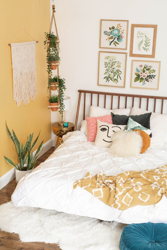 a spring boho bedroom with a yellow statement wall, printed bedding, a floral gallery wall and potted plants