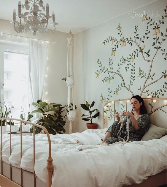 a spring boho bedroom with neutral walls, a neutral metal bed, a white chandelier, a painted tree, potted greenery