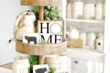 a spring farmhouse stand with greenery, beads, funny artworks of wood and a little gnome for kitchen decor