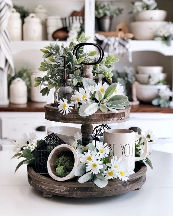 a spring kitchen stand of reclaimed wood, with pale greenery and blooms, moss and some mugs