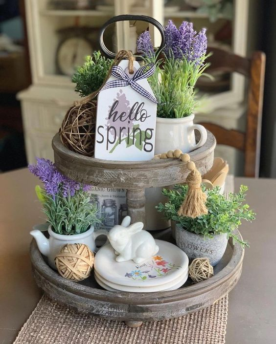 a spring kitchen stand with purple blooms, vine balls, greenery, bunnies and floral plates