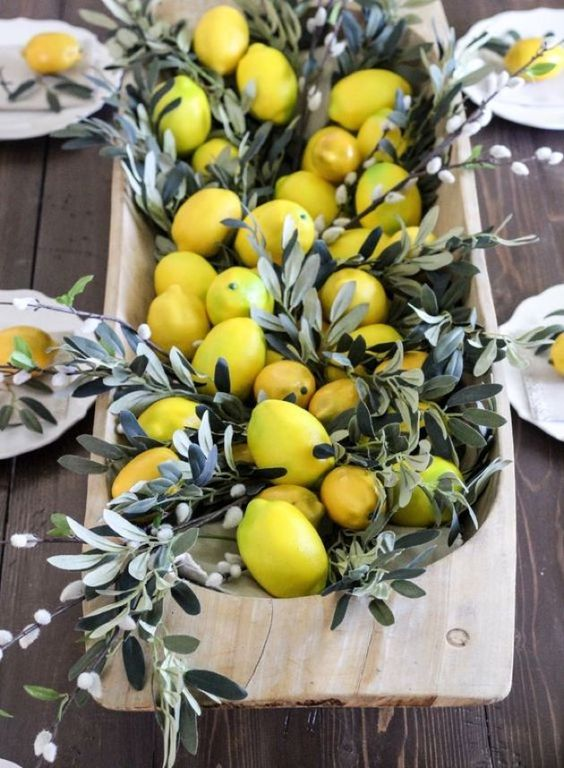 a spring or Easter centerpiece of a wooden breadbowl with lemons and willow