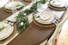 a spring or Easter tablescape with greenery runner, white tulips, wicker chargers and plaid napkins