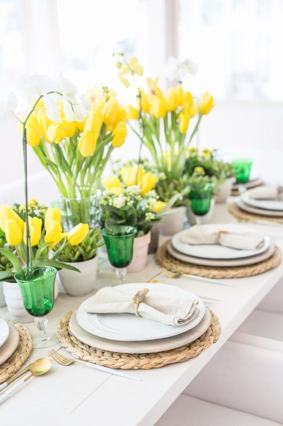 a spring tablescape with bright yellow tulips, fresh greenery and green glasses looks bold, fresh and very spring like
