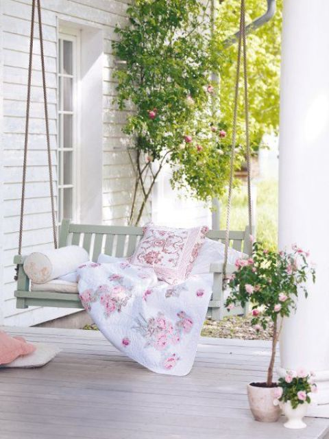 a spring terrace with a suspended daybed, floral bedding, potted blooms and greenery is airy and welcoming