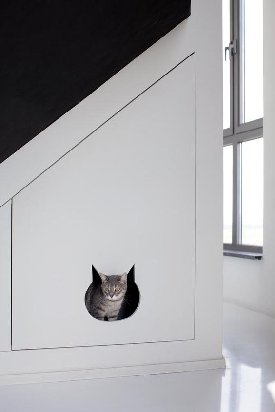a staircase with a built-in cat toilet - it's a large sleek drawer with a cat head entrance is perfect for a minimalist space