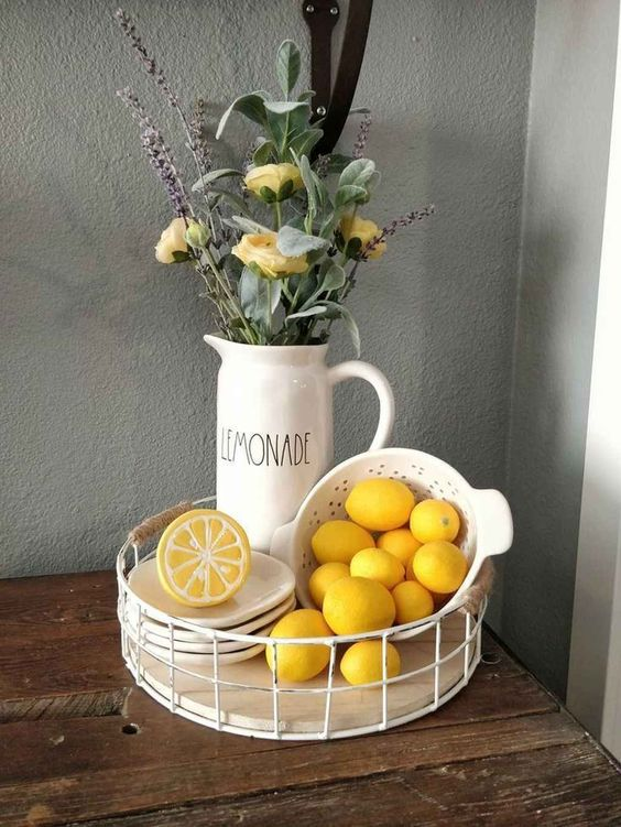 a stand with lemons, a toy lemon and an arrangement of greenery, yellow roses and lavender for spring decor
