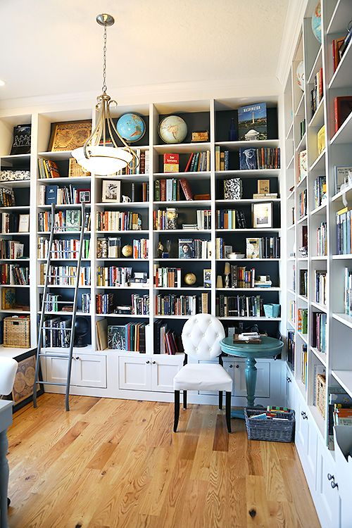 a stylish home office and library in one with built-in bookshelves, a white chair, a pendant lamp and some vintage items
