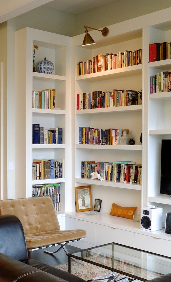a stylish mid-centrury modern living room with built-in bookshelves and additional lamps over the space