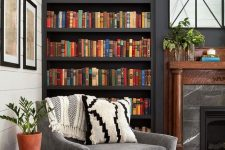 a stylish moody space with dark built-in bookshelves, a marble fireplace and a grey chair for much comfort