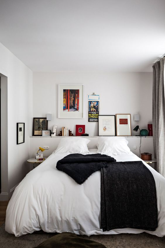 a stylish small bedroom with a cool gallery wall, a bed and mismatching nightstands for a chic look