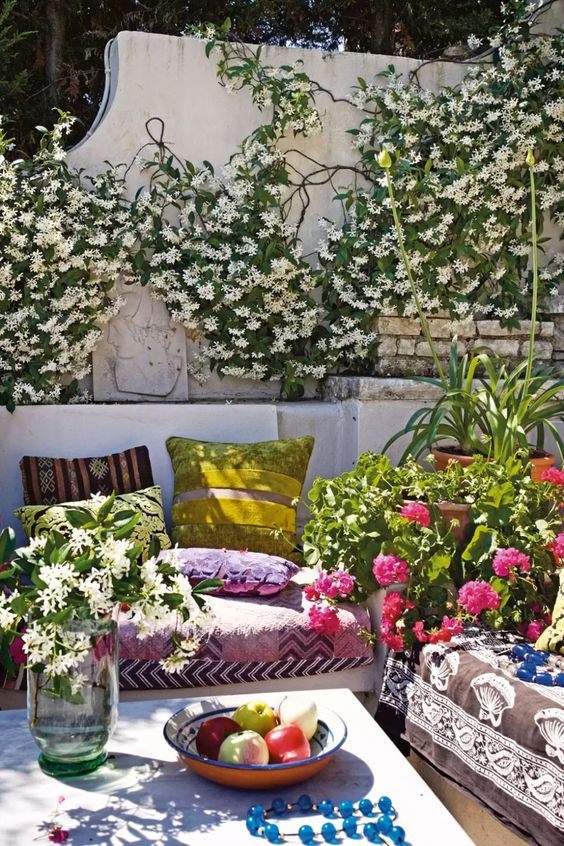 a super bold spring terrace with greenery and blooms, with colorful textiles, potted plants and colorful pillows