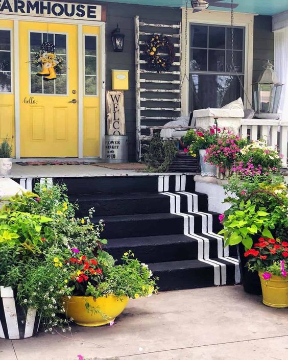 a super bright spring porch with potted blooms and greenery looks really cheerful and fun