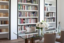 a super refined home office with built-in bookshelves with black framing to accent them as much as possible