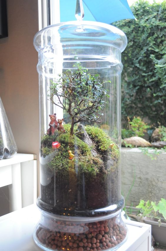 a tall jar with a scenery - moss hills, a mini tree, wood and bears and a duck is a cute idea for a child's room