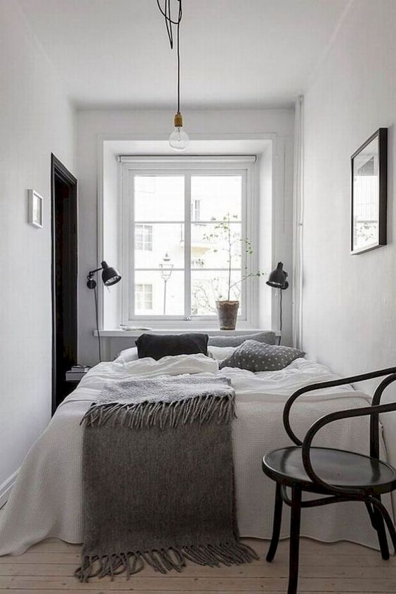 a tiny Scandinavian bedroom with black sconces, a black chair and a bed with comfy bedding