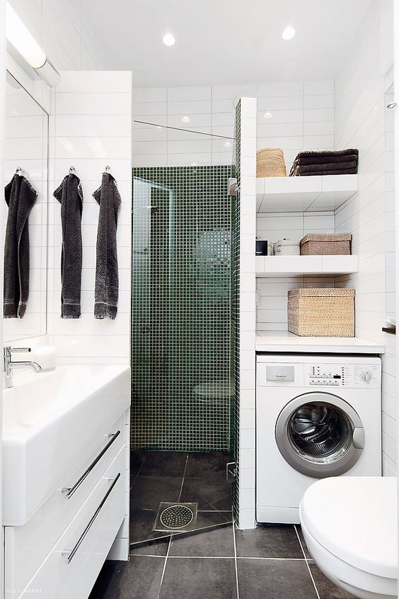 a tiny contemporary bathroom with a tiled shower space, a washing machine, a white vanity and a sink
