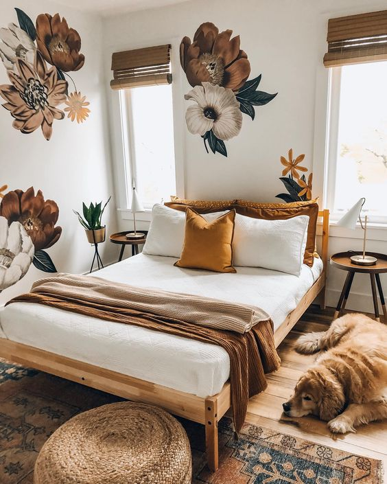 a tiny earthy bedroom with floral decals, wooden furniture, a rattan ottoman and a boho rug