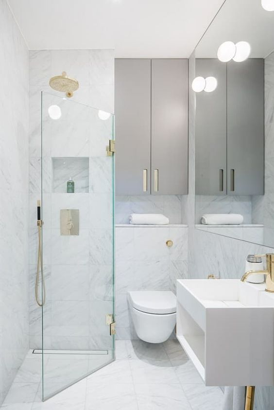 a tiny minimalist bathroom with white marble tiles, sleek grey cabinets, gilded touches and a triangle shower space