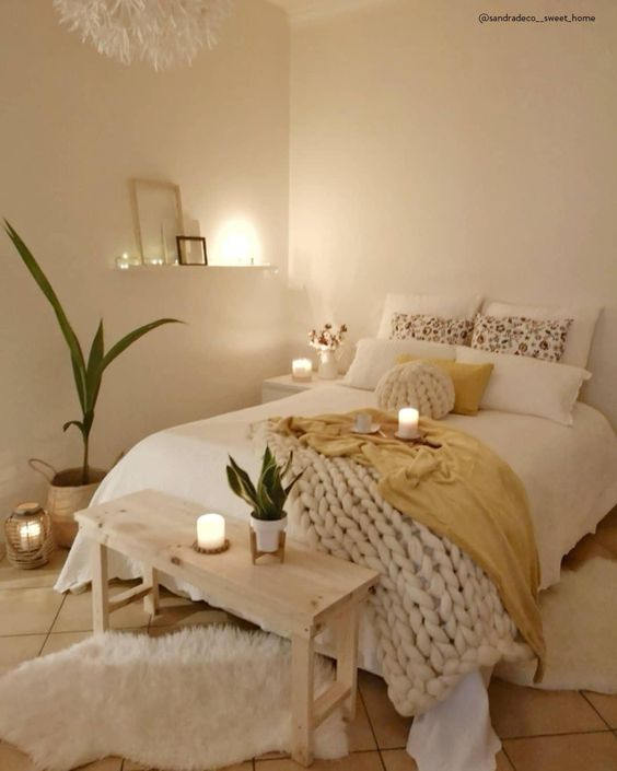 a tiny neutral bedroom with catchy bedding and a chunky knit blanket, a wooden bench, potted greenery and candles