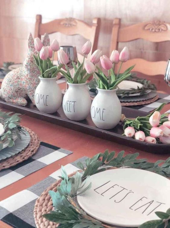 a tray with a floral bunny, pink tulips in vases and greenery wreaths for each place setting feel spring-like