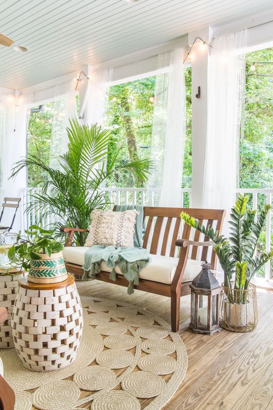a tropical boho porch with wooden furniture, jute rugs, lots of potted greenery and candle lanterns