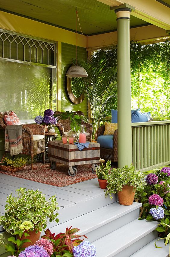 a tropical boho porch with woven furniture, a wooden coffee table, potted greenery and colorful textiles