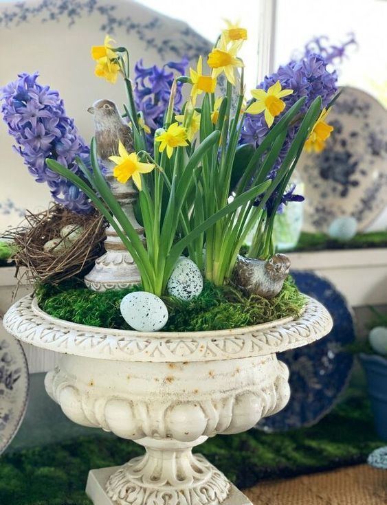 a vintage urn with moss, fake eggs and a nest, purple hyacinths and yellow daffodils for a rustic feel and a spring touch