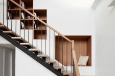 a wall with built-in bookshelves and a niche seat is a genius idea to rock over the stairs