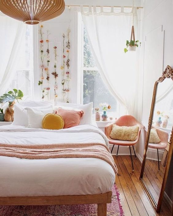 a warm spring bedroom with a wooden bed, a pink chair, pink and yellow pillows, faux blooms attached to the wall
