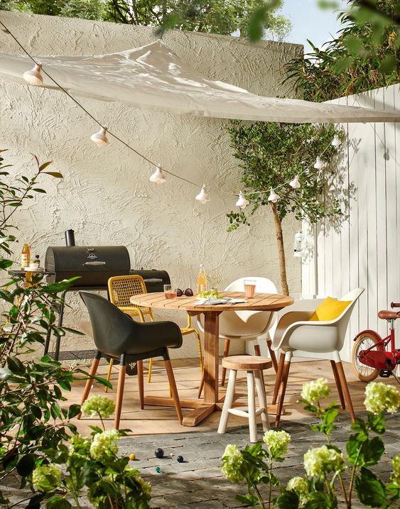 a welcoming sprign terrace with a modern wooden table and mismatching chairs, potted greenery and blooms and some lights over the space