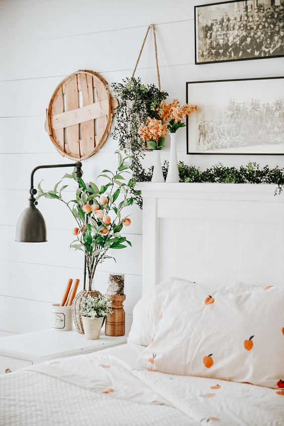 a welcoming spring bedroom in neutrals, with pretty artworks, greenery and blooms, a wall sconce, printed bedding