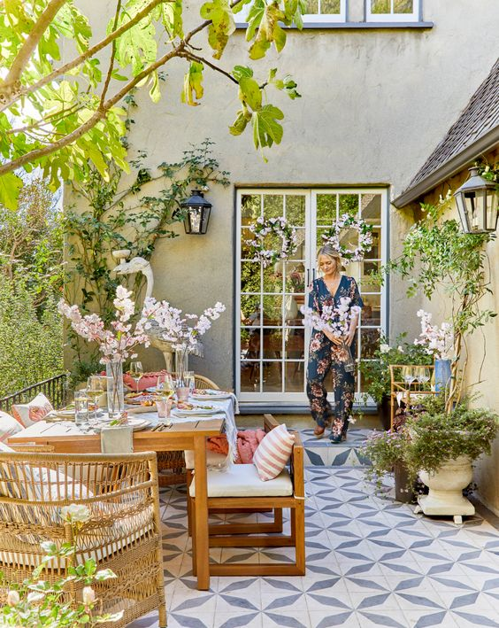 a welcoming spring terrace with potted greenery and blooms, with colorful textiles and wooden and wicker furniture