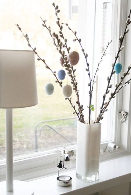 a white vase with willow and colorful and pastel eggs hanging on them will be a nice Easter decoration