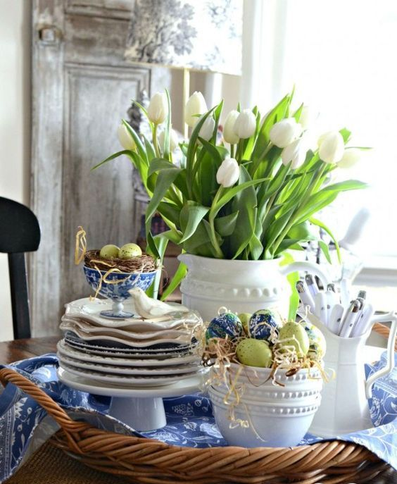 a wicker tray with blue linens, a nest with eggs and a bowl with them and a jar with white tulips for a spring and Easter look