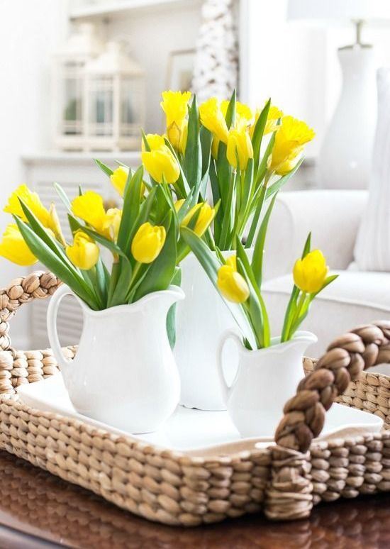 a wicker tray with several matching white jugs and bright yellow tulips for a bold springy look