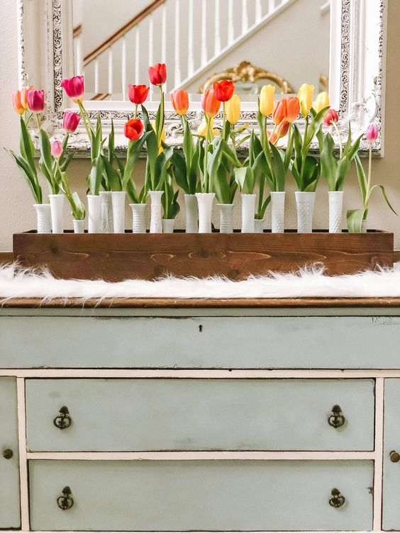 a wooden box, white textural vases and a whole arrangement of bright spring tulips is a bold decoration for spring