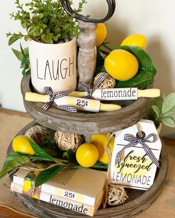 a wooden stand with faux lemons, greenery and potted greenery plus some lemonade signs for a spring feel