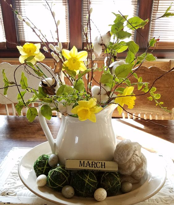 an amazing spring centerpiece of a bowl with moss balls and fake eggs, a jug with greenery, willow and daffodils and cotton