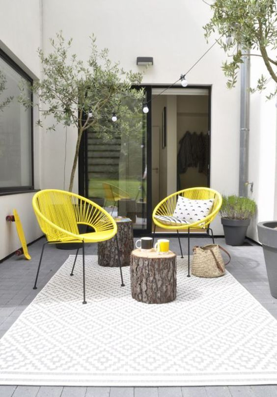 an eclectic spring terrace with neon yellow chairs, tree stumps, potted greenery and plants and printed pillows