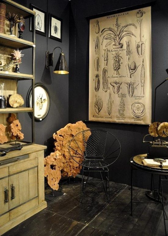 an elegant Gothic home office with black walls, a rustic wooden storage unit with open shelves, a vintage poster and metal furniture