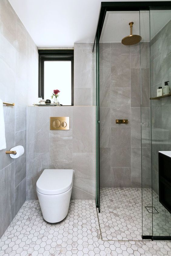 an elegant contemporary bathroom with stone and marble tiles, a window, a shower space and gilded touches