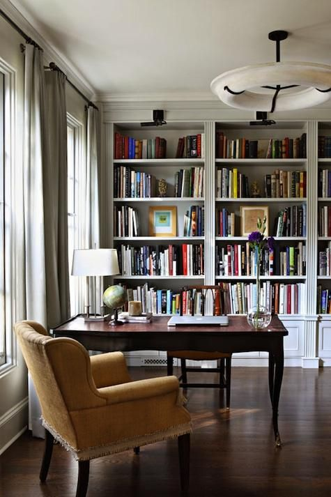 an elegant home office with built-in bookshelves, a refined desk and chair is a cool place to be