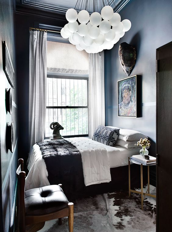 an elegant moody bedroom with dark walls, a catchy chandelier, artworks, an animal rug and leather chairs