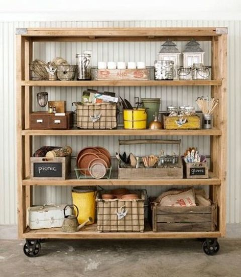 an oversized wooden shelving unit with metal wheels is a great idea to store and see everything you place there at the same time