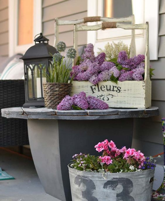 bold blooms in a tool box and in a galvanized bucket plus candle lanterns for a bright spring porch