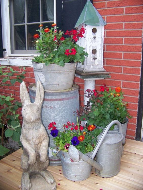 bright blooms in galvanized buckets, a bunny statue and a bird house for a rustic vintage spring porch